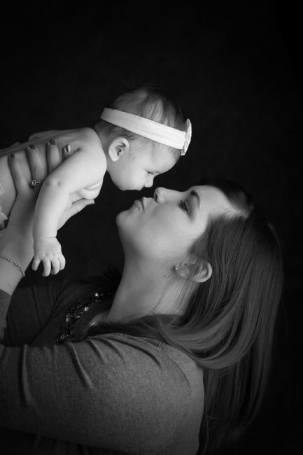black and white photo of mother holding baby girl up in the air