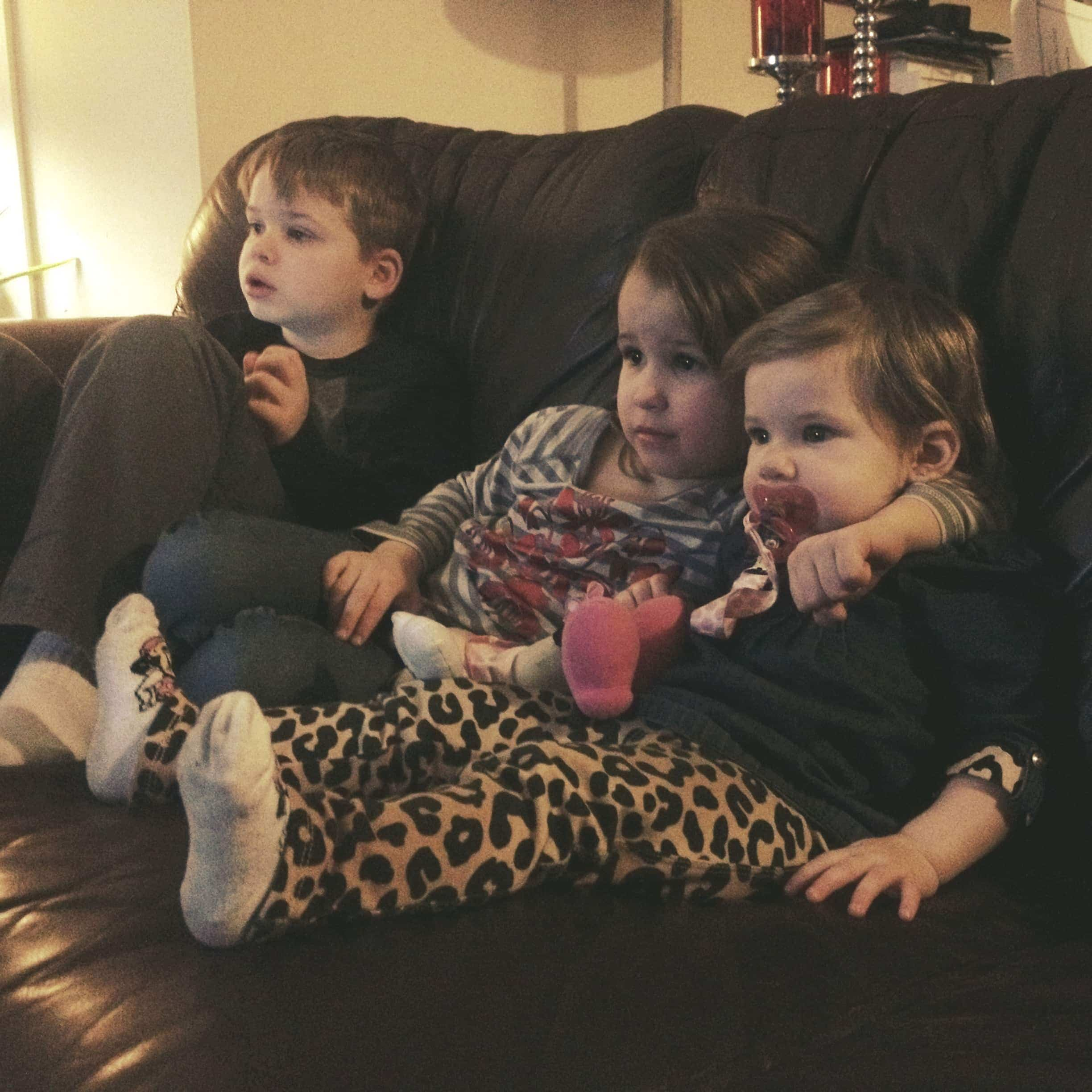 3 cousins sitting together and cuddling on leather couch