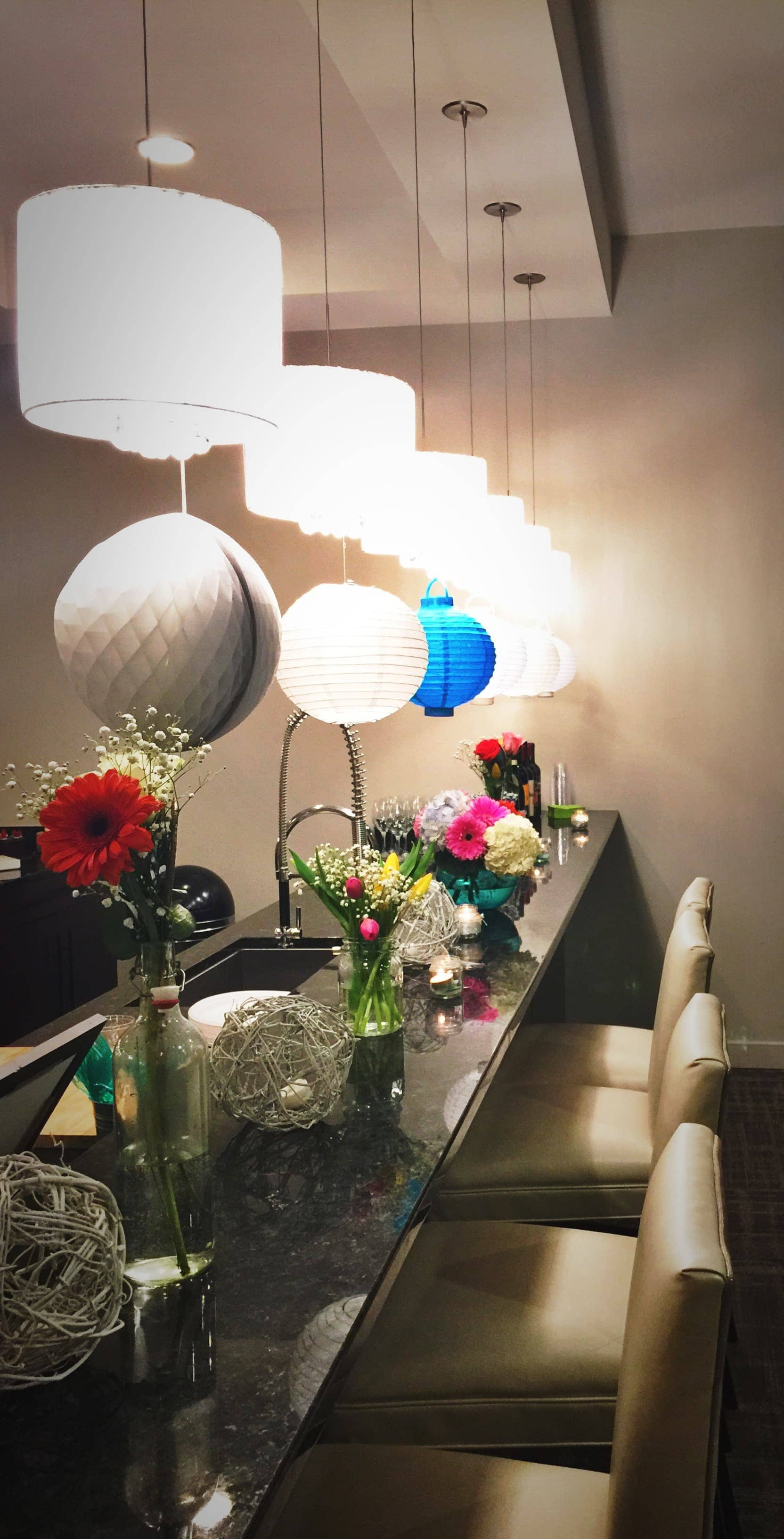 baby shower with flowers on counter and paper lanterns having from lights