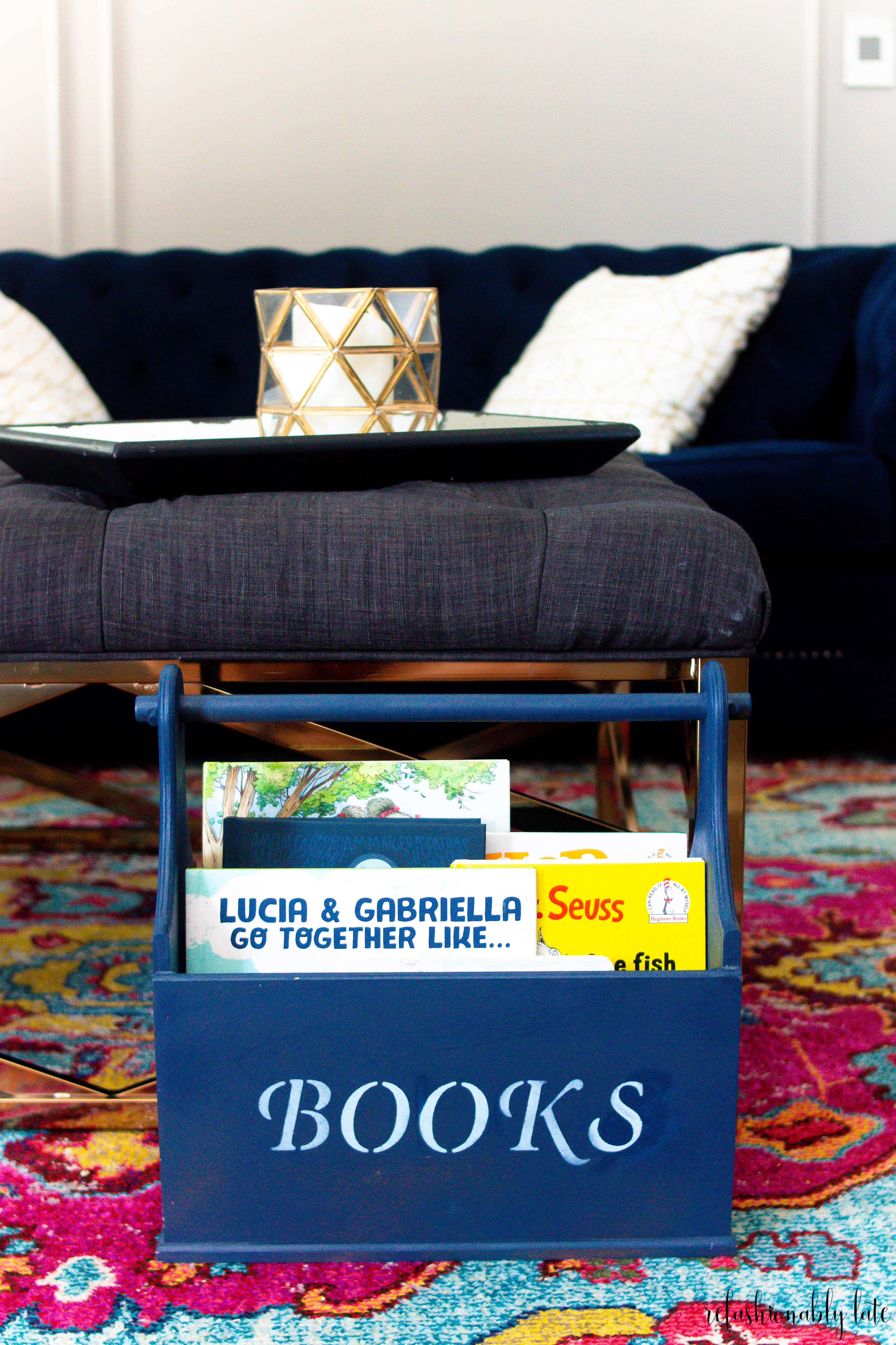 blue book storage with children's books inside on top of colorful rug