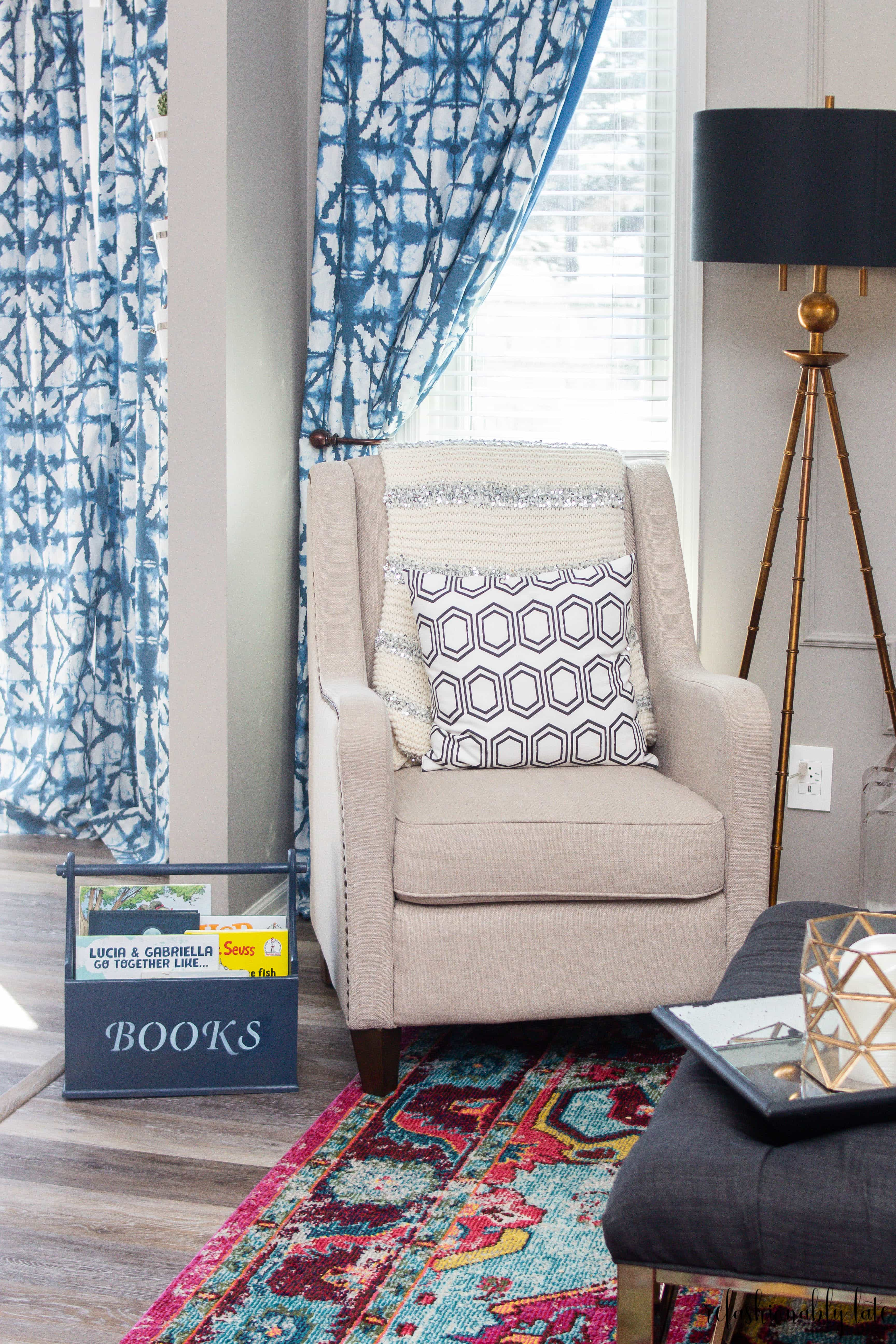 blue book storage in living room with tan chair and shibori curtains