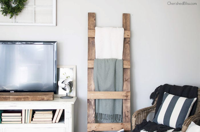 DIY wood ladder with blankets hanging on it against the wall