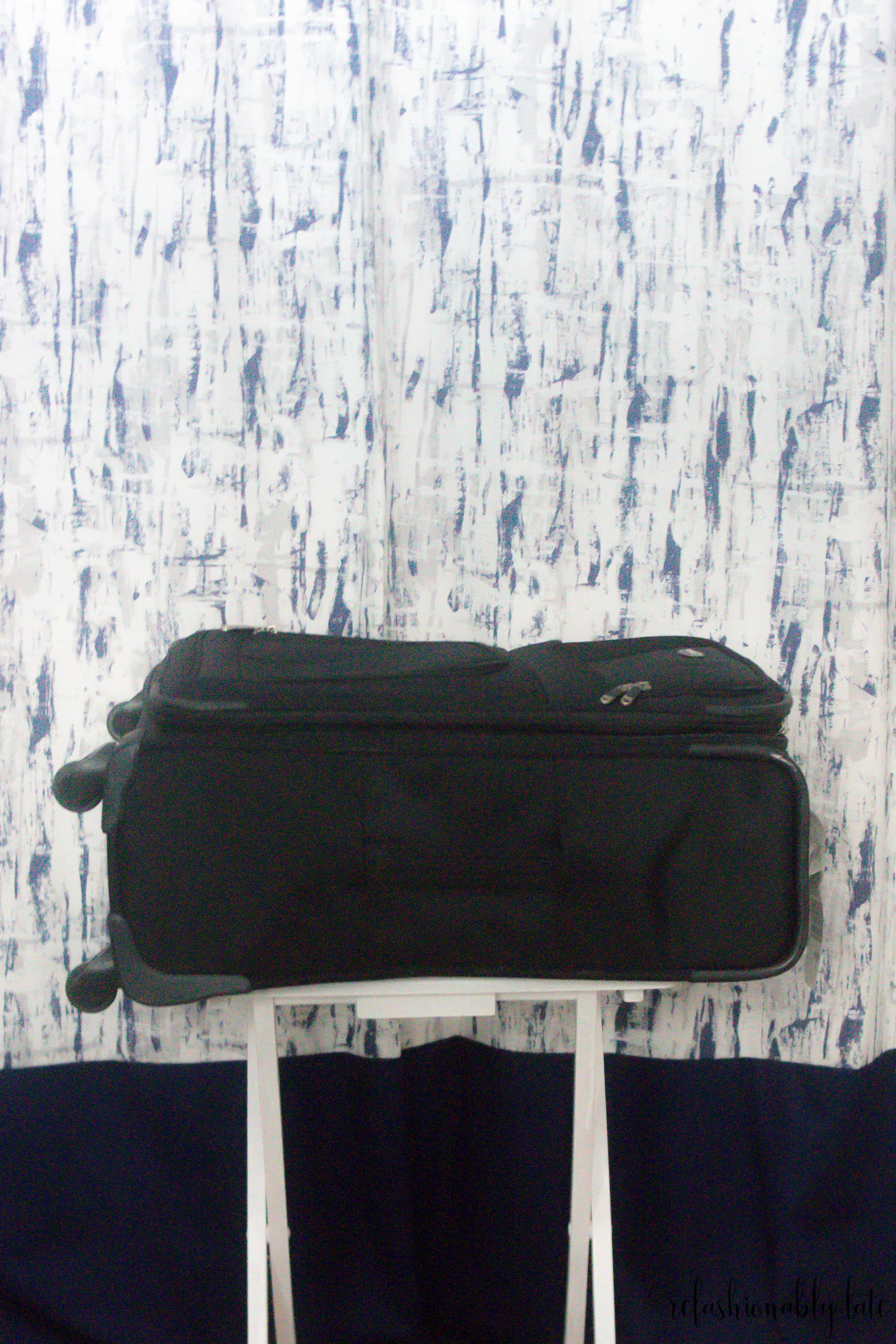 black suitcase on top of a DIY luggage rack with blue curtains behind it