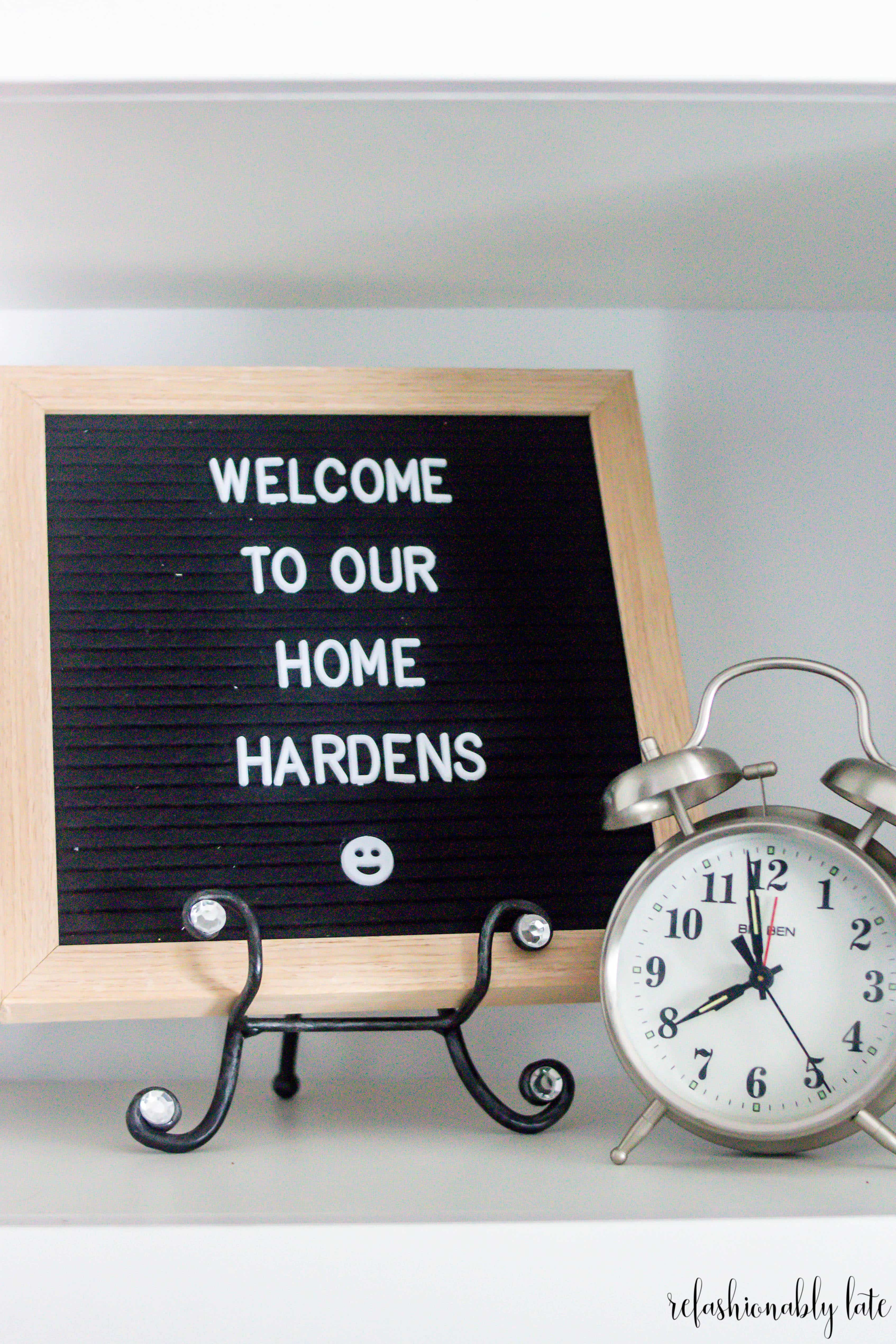 letter board reading welcome to our home hardens with an alarm clock on the side