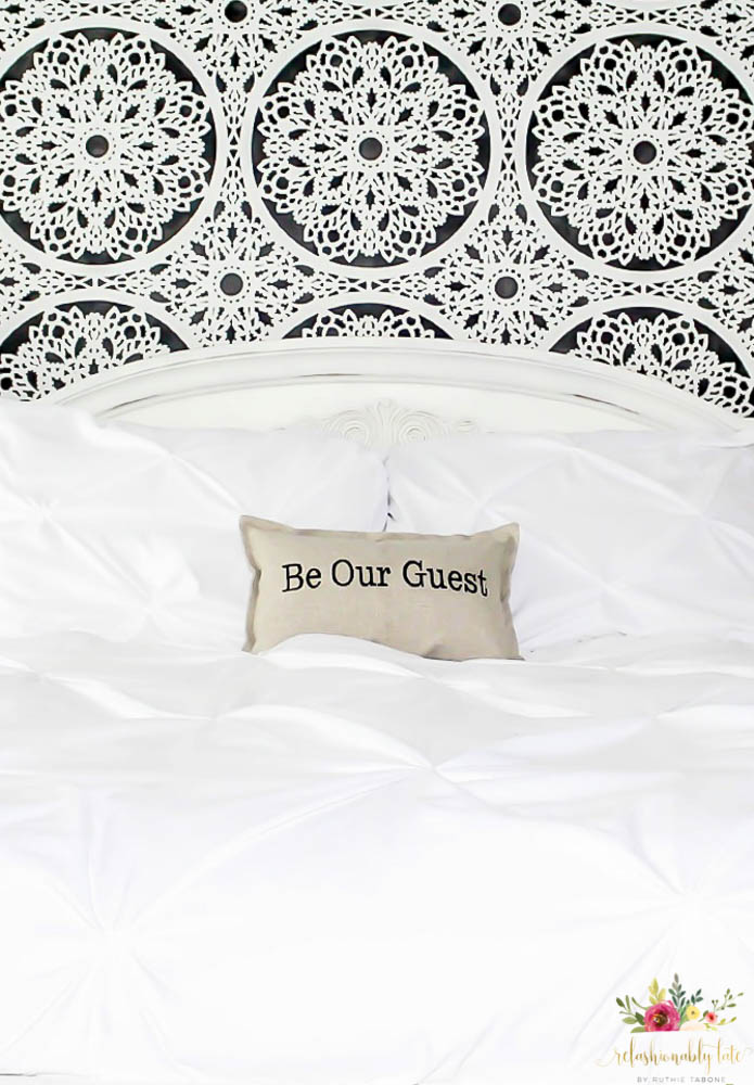 black and white wall with white bead and a tan pillow reading Be Our Guest