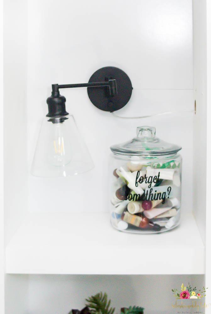 shelf with guest room jar reading forget something on the front with a moving light next to it