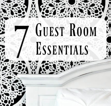 black and white stenciled feature wall with white bed and text overlay reading 7 guest room essentials