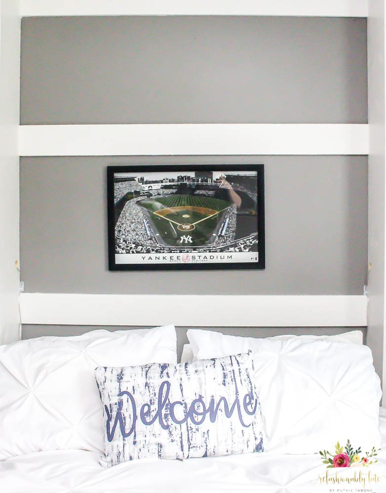 white murphy bed folded down with a white duvet and a blue and white pillow with word Welcome on it with gray walls and a yankee stadium picture