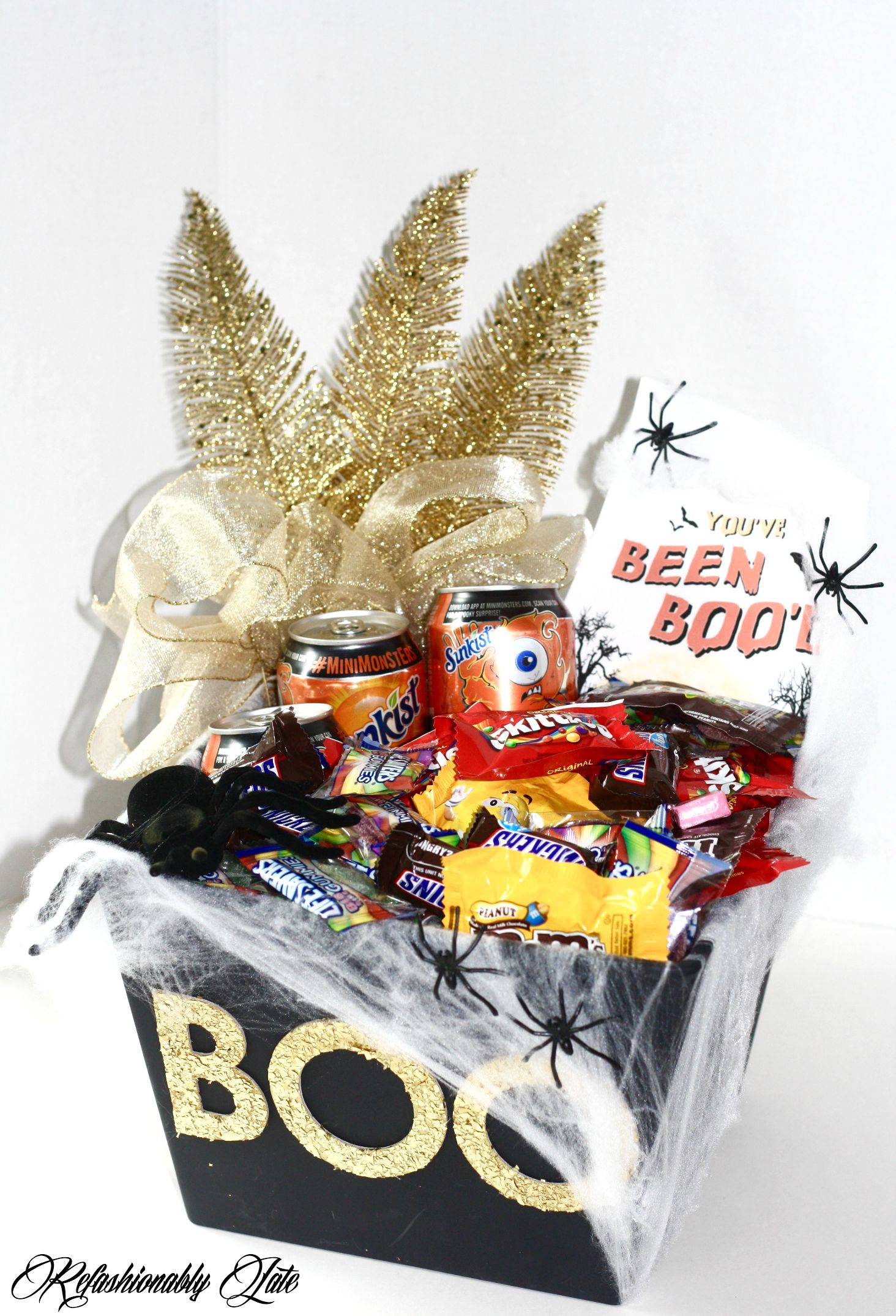 basket with the word BOO on the front filled with candy and gold decorations