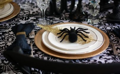 Spider sitting on top of a white china and a gold charger on a damask tablecloth