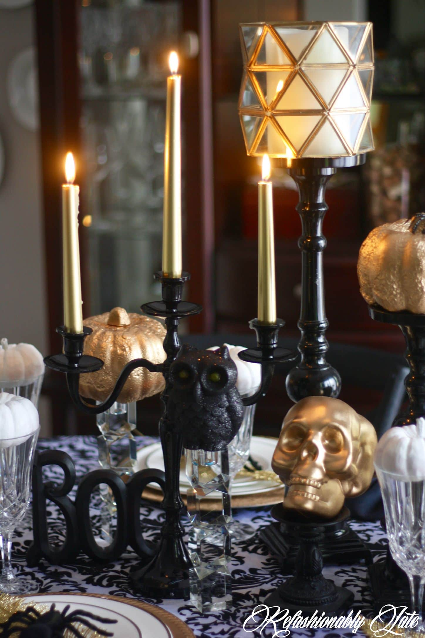 Halloween decor including a skull boo sign candles and pumpkins sitting on a damask table cloth
