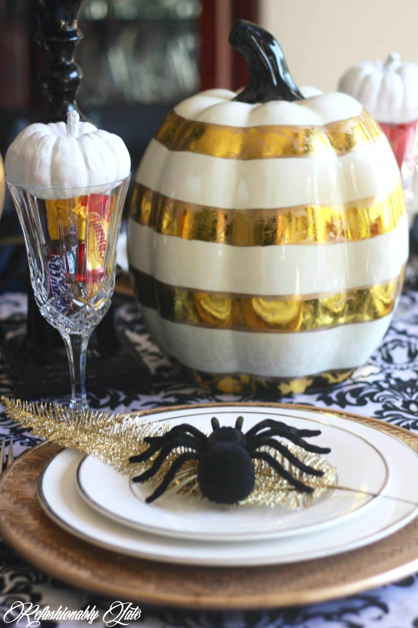 Gold and white striped pumpkin sitting on a damask tablecloth with a place setting in front of it