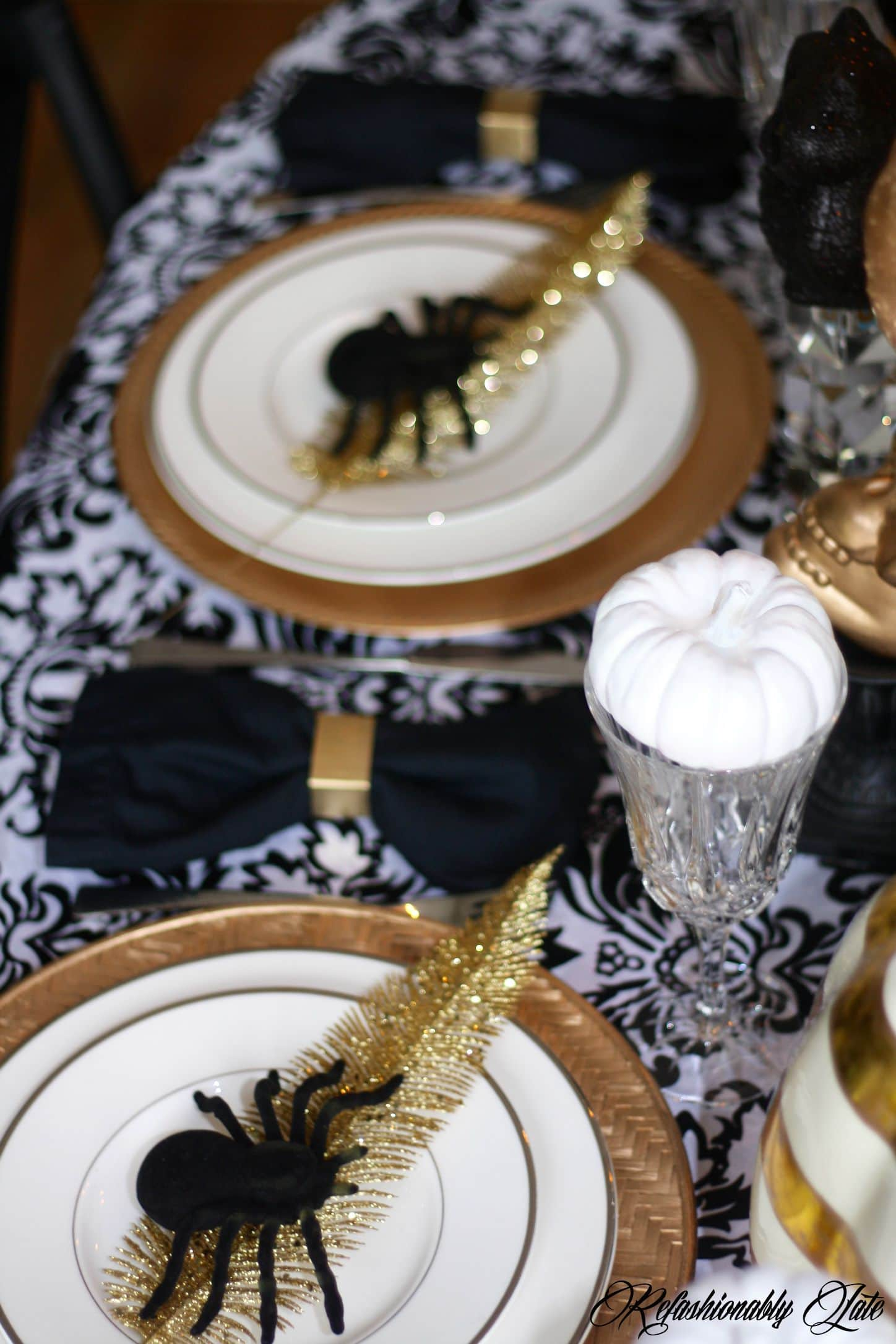 fake spiders on top of a gold leaf on place setting