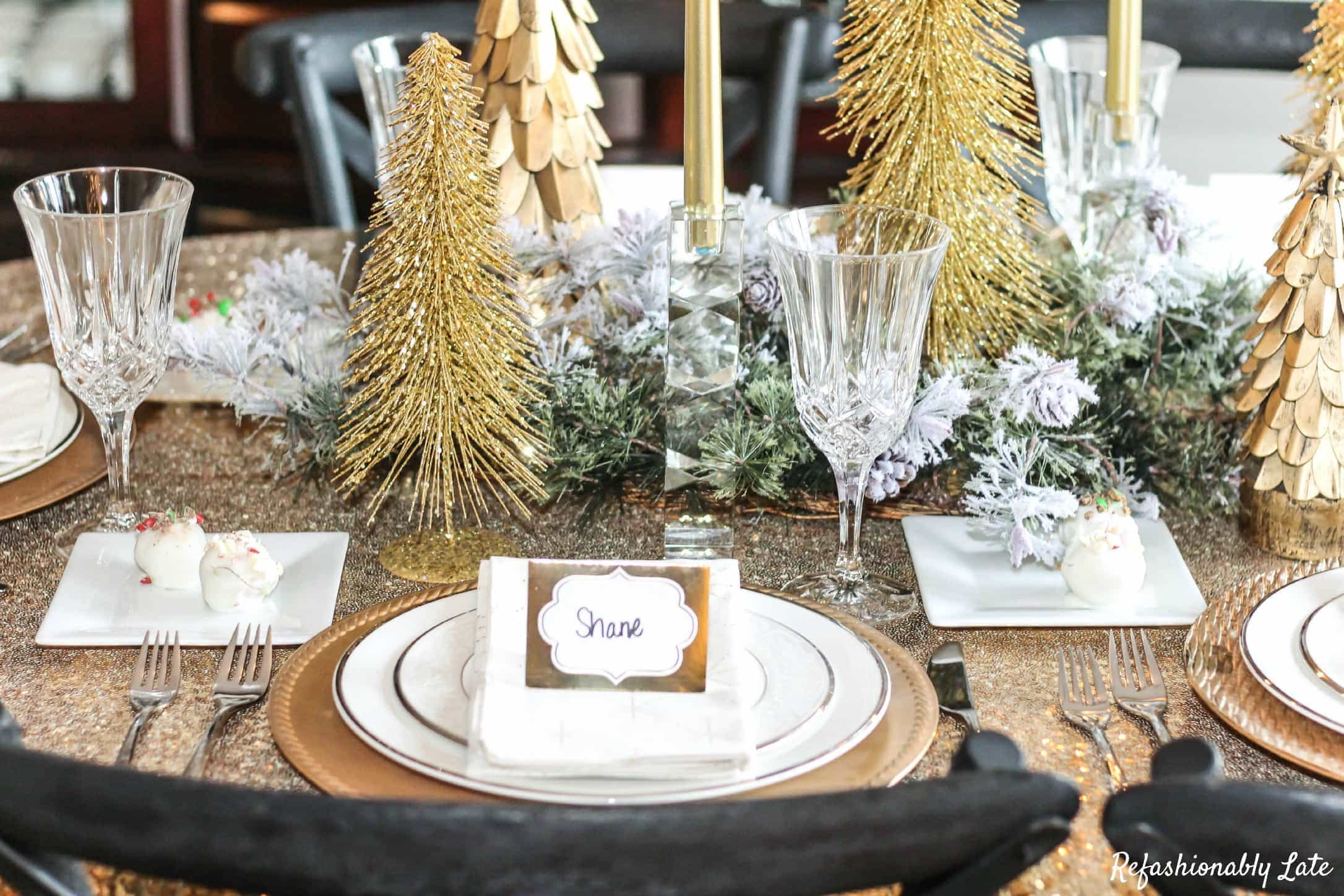 gold sequin tablecloth with gold chargers and white plates and gold trees with other gold white and green accents