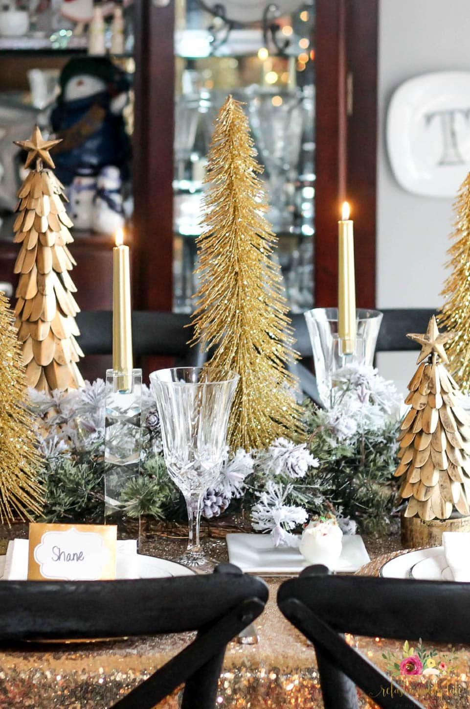 gold trees sitting on top of a gold sequin tablecloth with crystal glasses and place cards with white china and gold candles