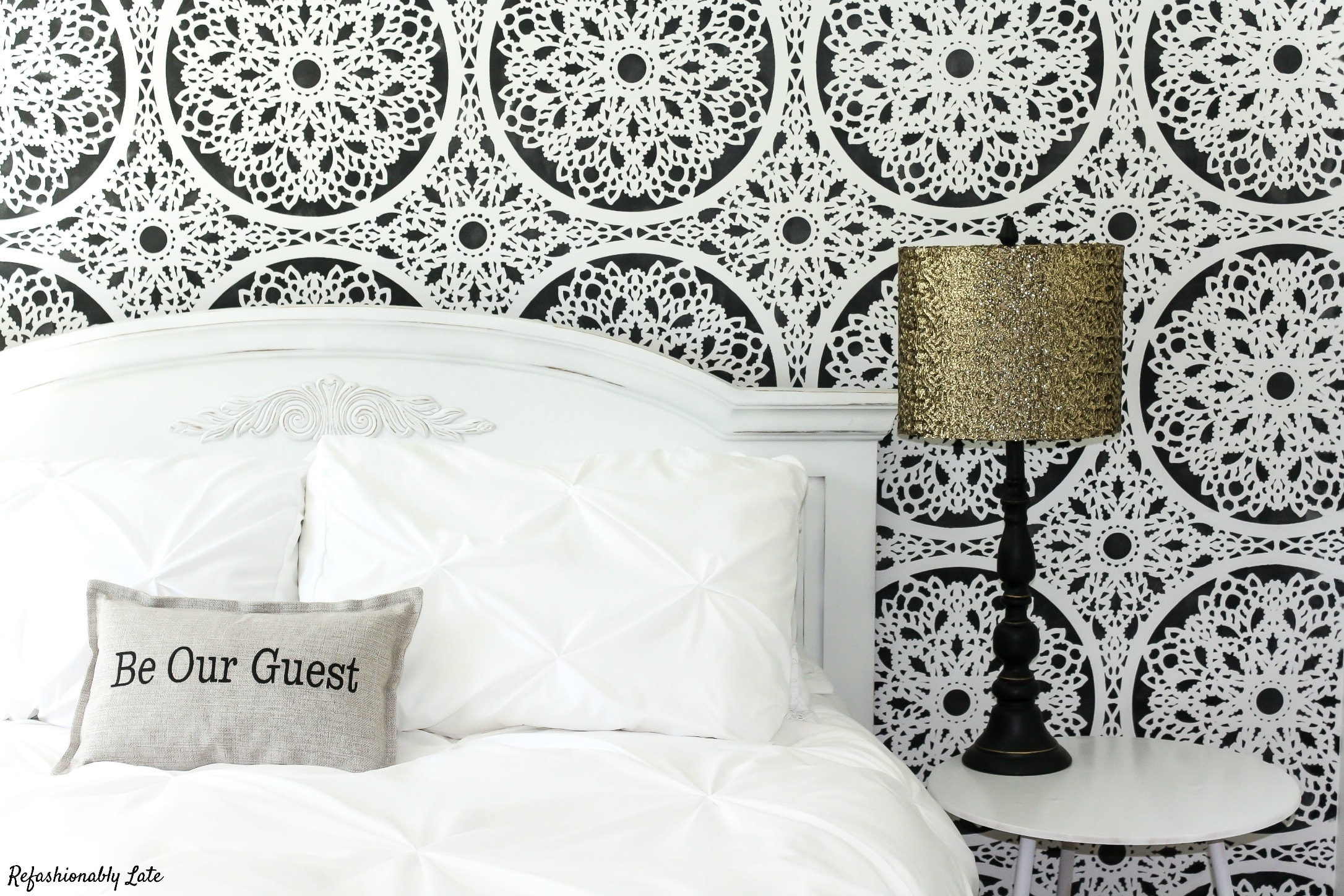 black and white stenciled wall with white bed and a lamp with a gold shade