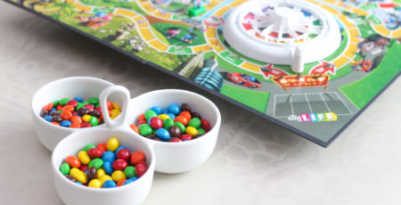 Container of M&Ms sitting in front of Life board game sitting on top of a DIY lazy susan