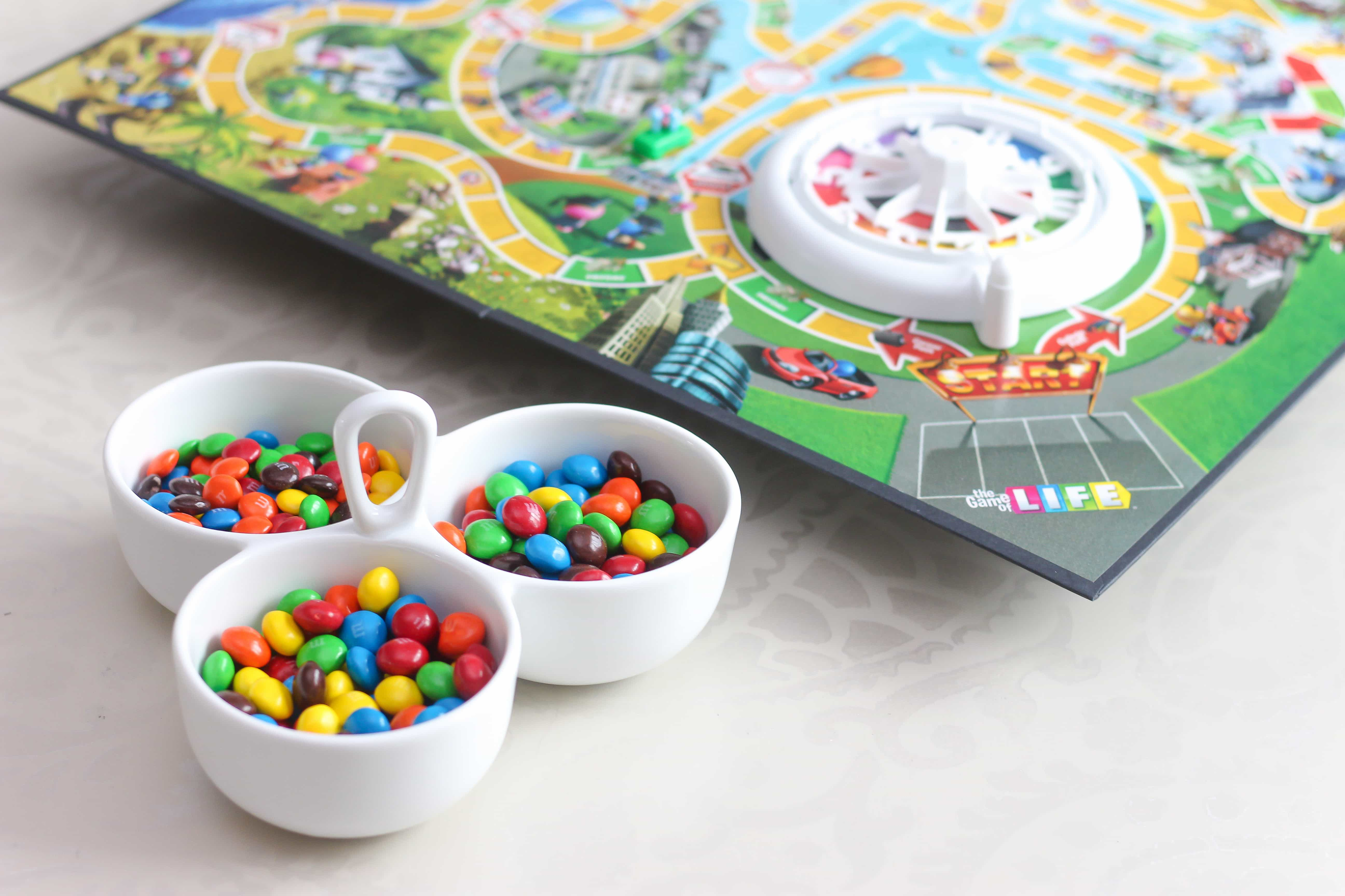 Bowls of M&Ms sitting on a white table with board game next to it