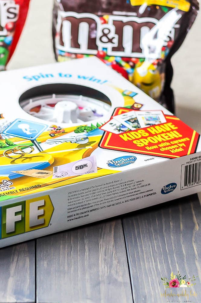 The Game of Life sitting on top of a lazy susan with M&Ms in the background