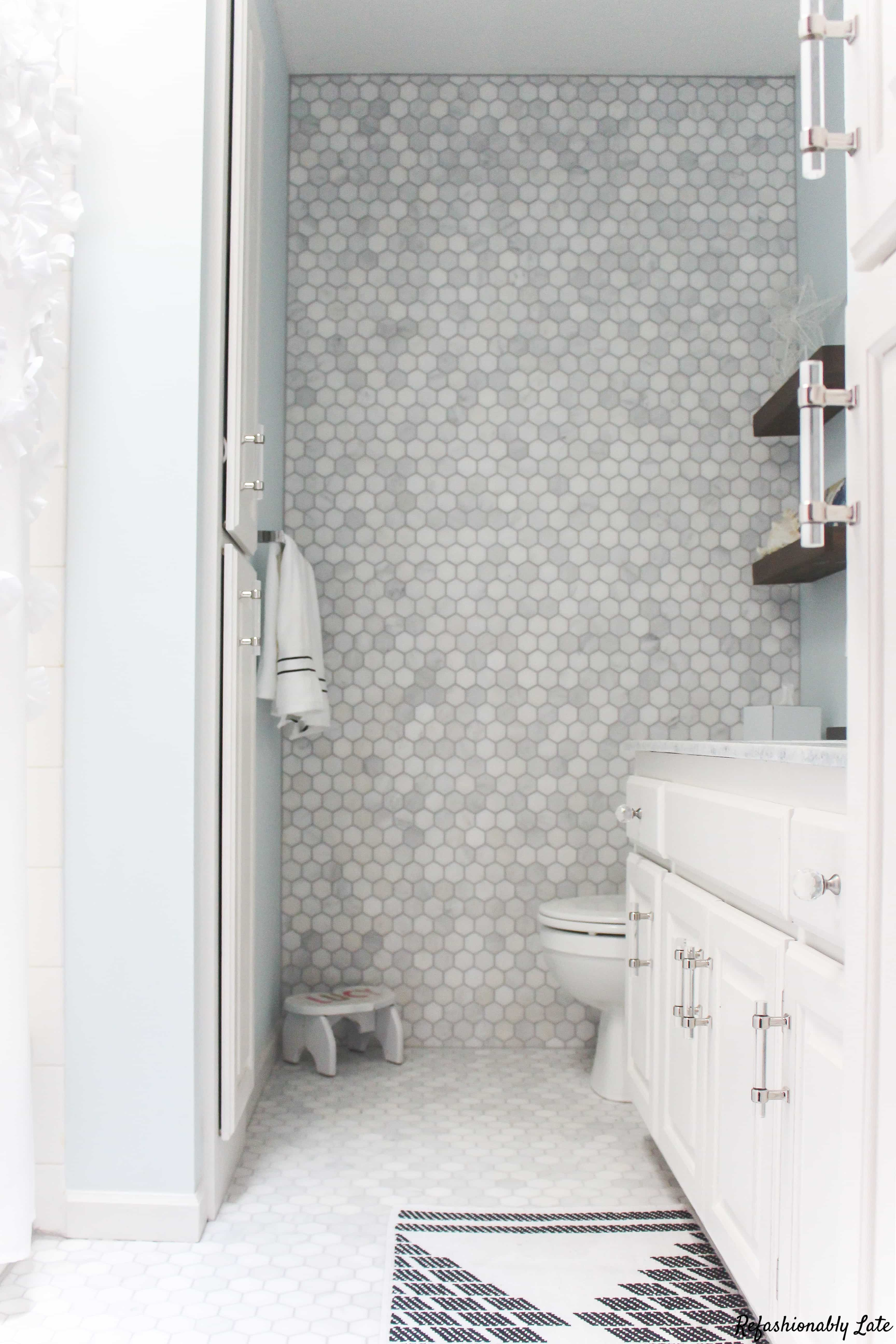 carrara marble floor and feature wall with blue walls and white cabinets