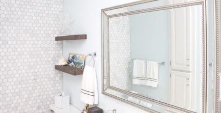 Constellation by Benjamin Moore on the walls with hexagon carrara marble tiled wall large mirror and marble countertop
