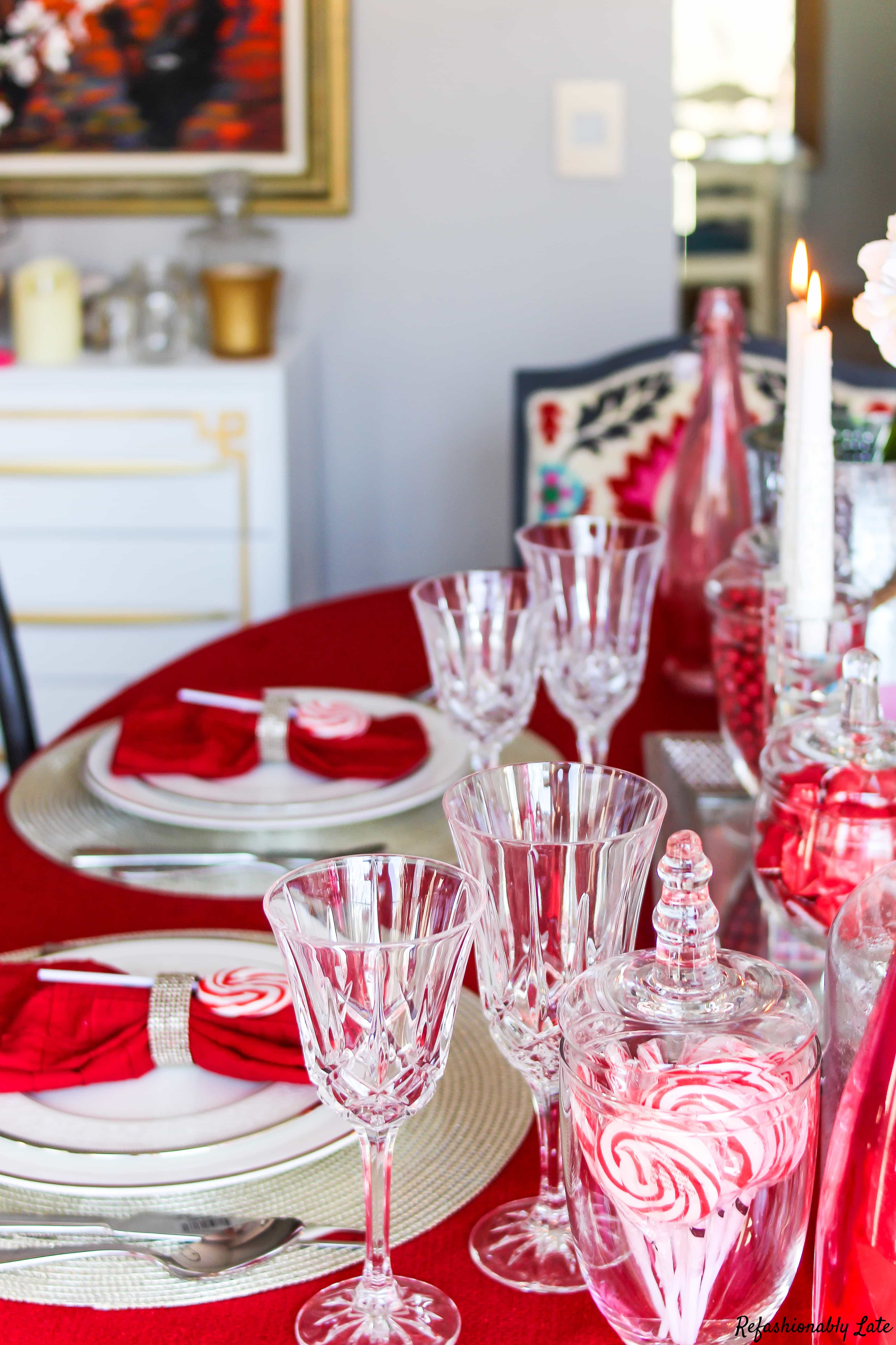beautiful valentines day tablescape with a bold red tablecloth and white and red accents and touches of light pink scattered throughout the table