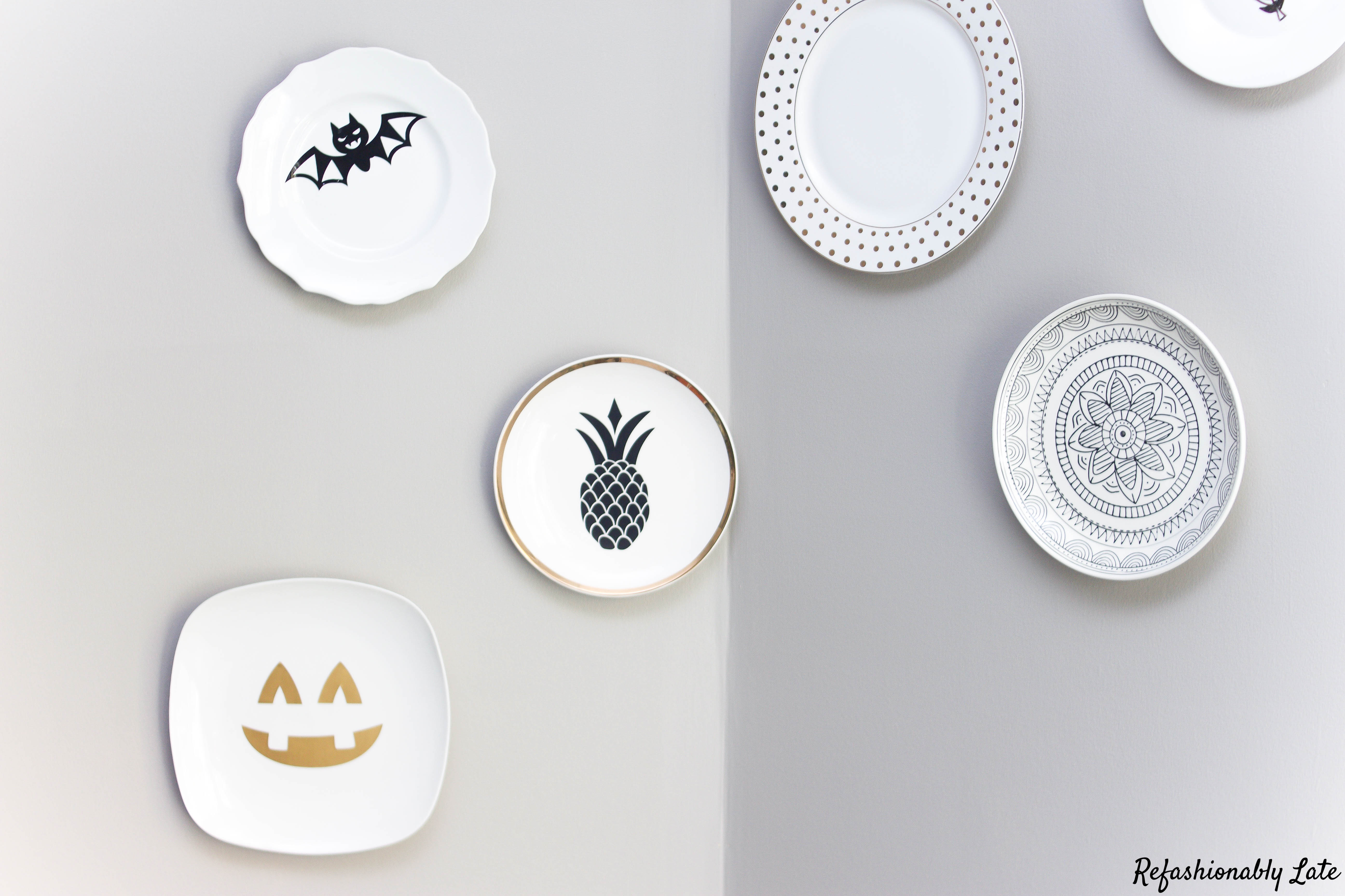 plates hung on a gray wall with Halloween window cling decals in the center of the plates