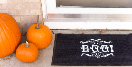 black doormat with the word BOO written on top sitting by 3 pumpkins on the front porch