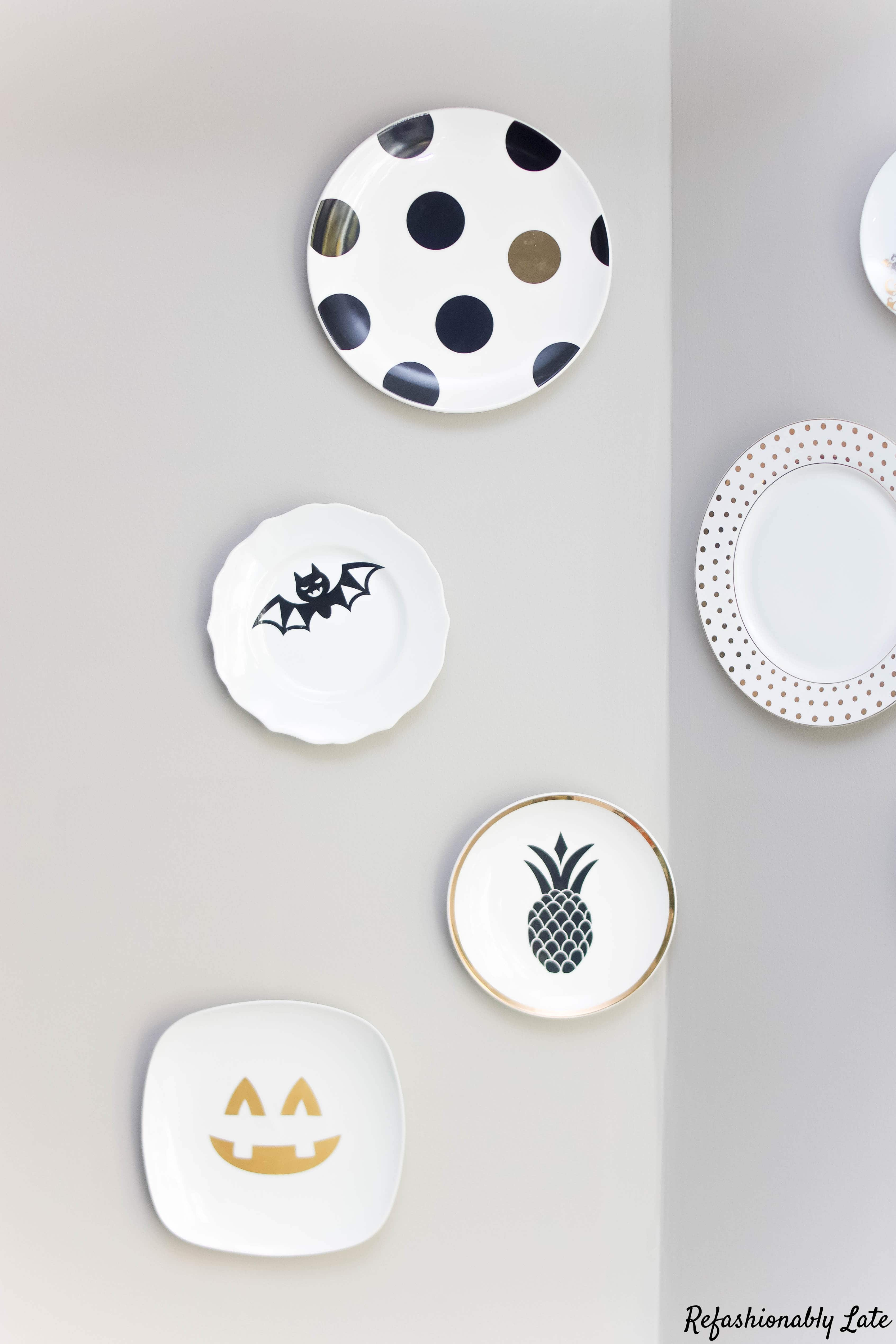 plates hung on a grey wall with decorative Halloween decals on the front