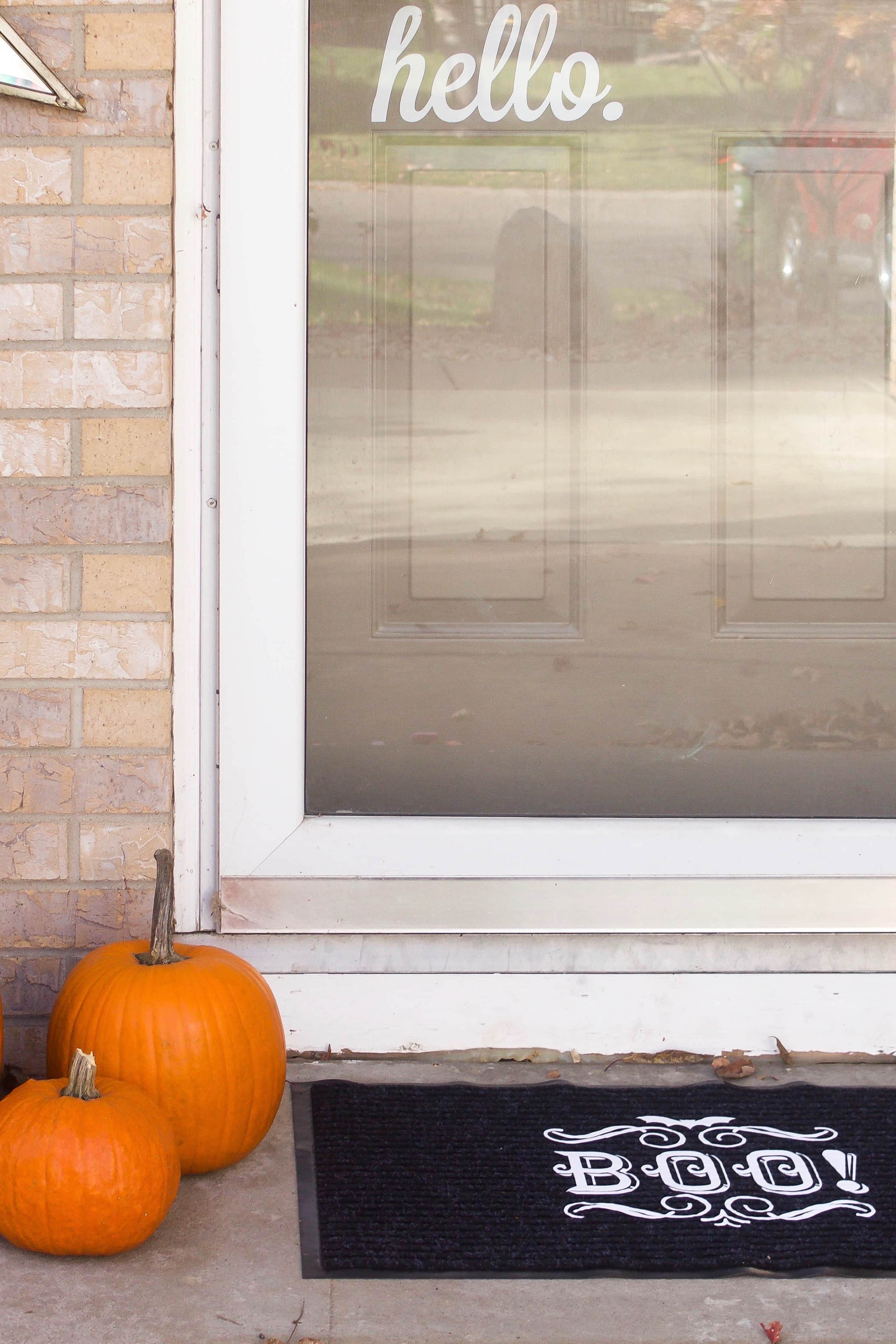 black doormat with BOO written on top sitting next to 2 pumpkins on the front porch