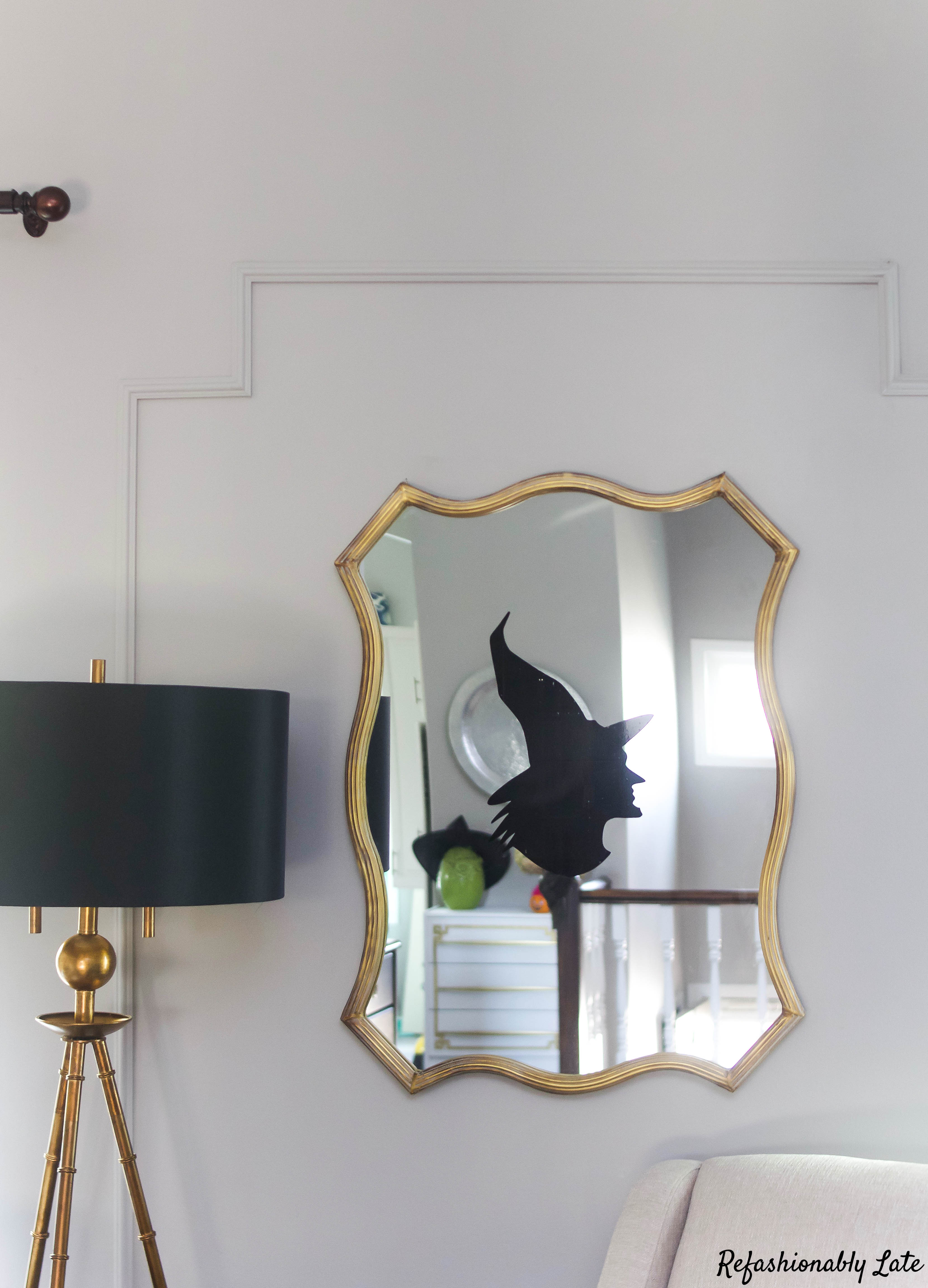 Gold mirror with a witch decal in the center on gray walls with a gold bamboo floor light with black shade