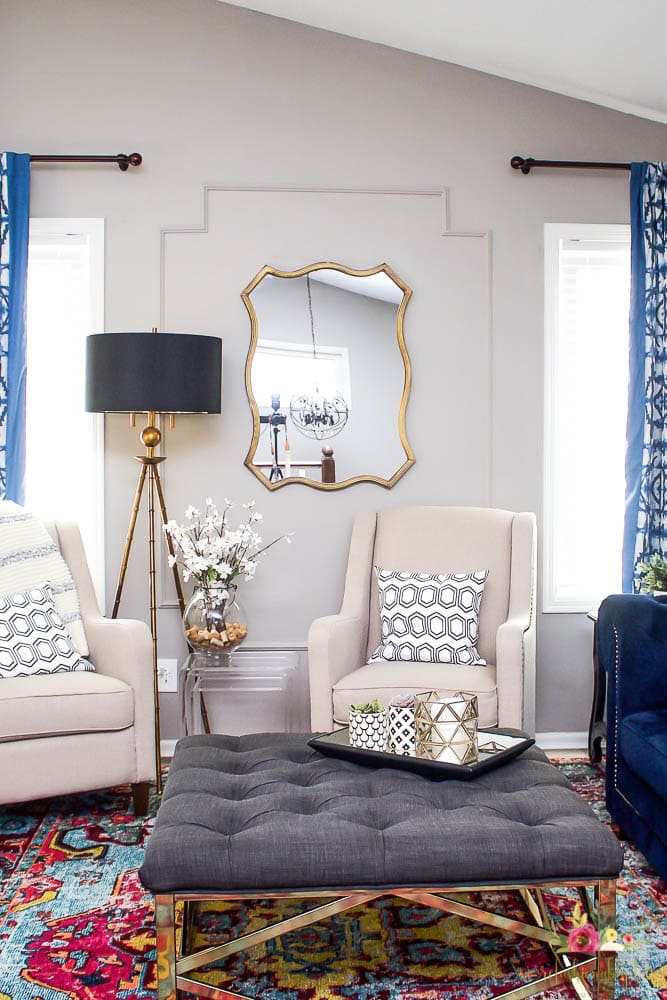 living room with tufted ottoman and linen chairs bright colored rug and gold mirror