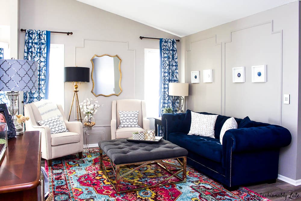 living room with navy chesterfield tufted ottoman and linen chairs with a gold mirror on the wall
