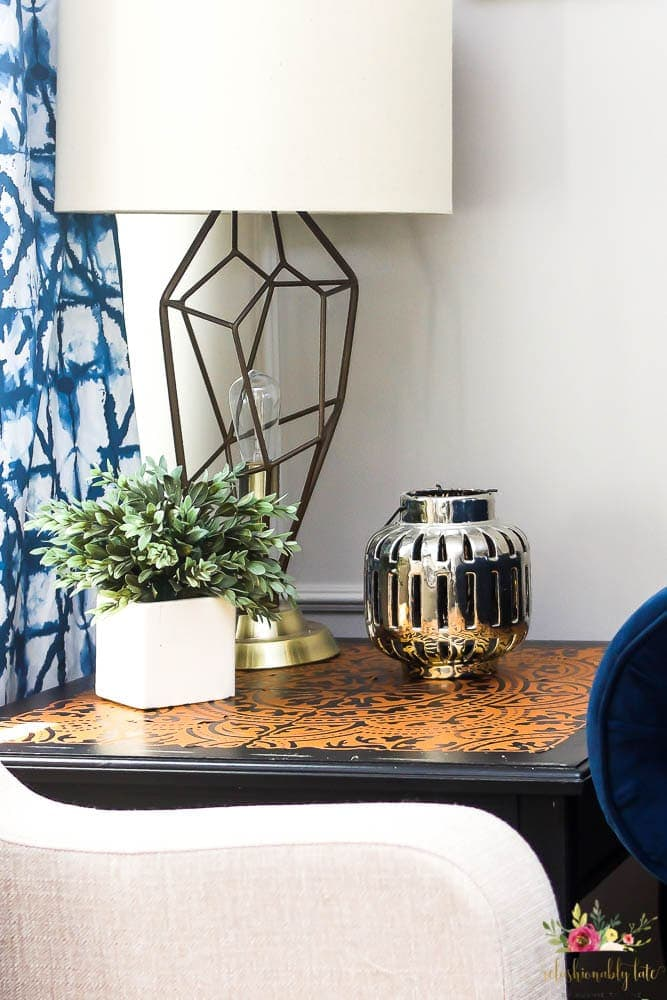 black end table with a gold foil design on the top and a lamp with a linen shade and a tufted navy chesterfield sofa