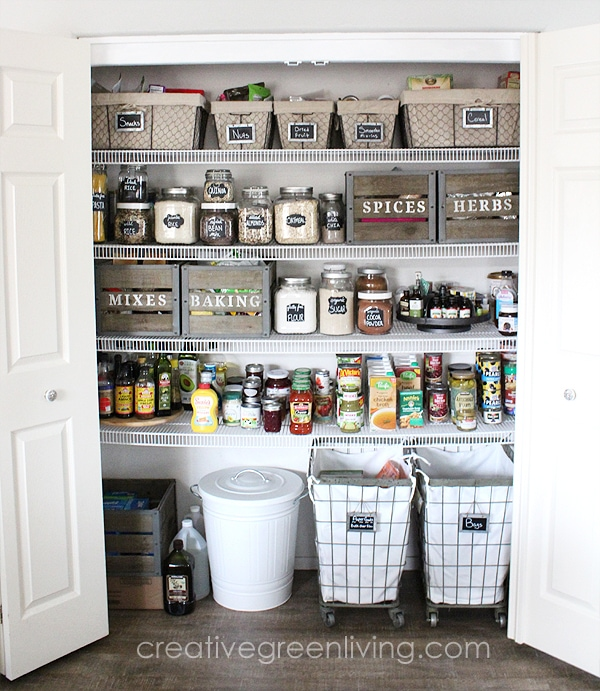 white doors opened to a large pantry with baskets jars and wooden boxes storing various pantry items