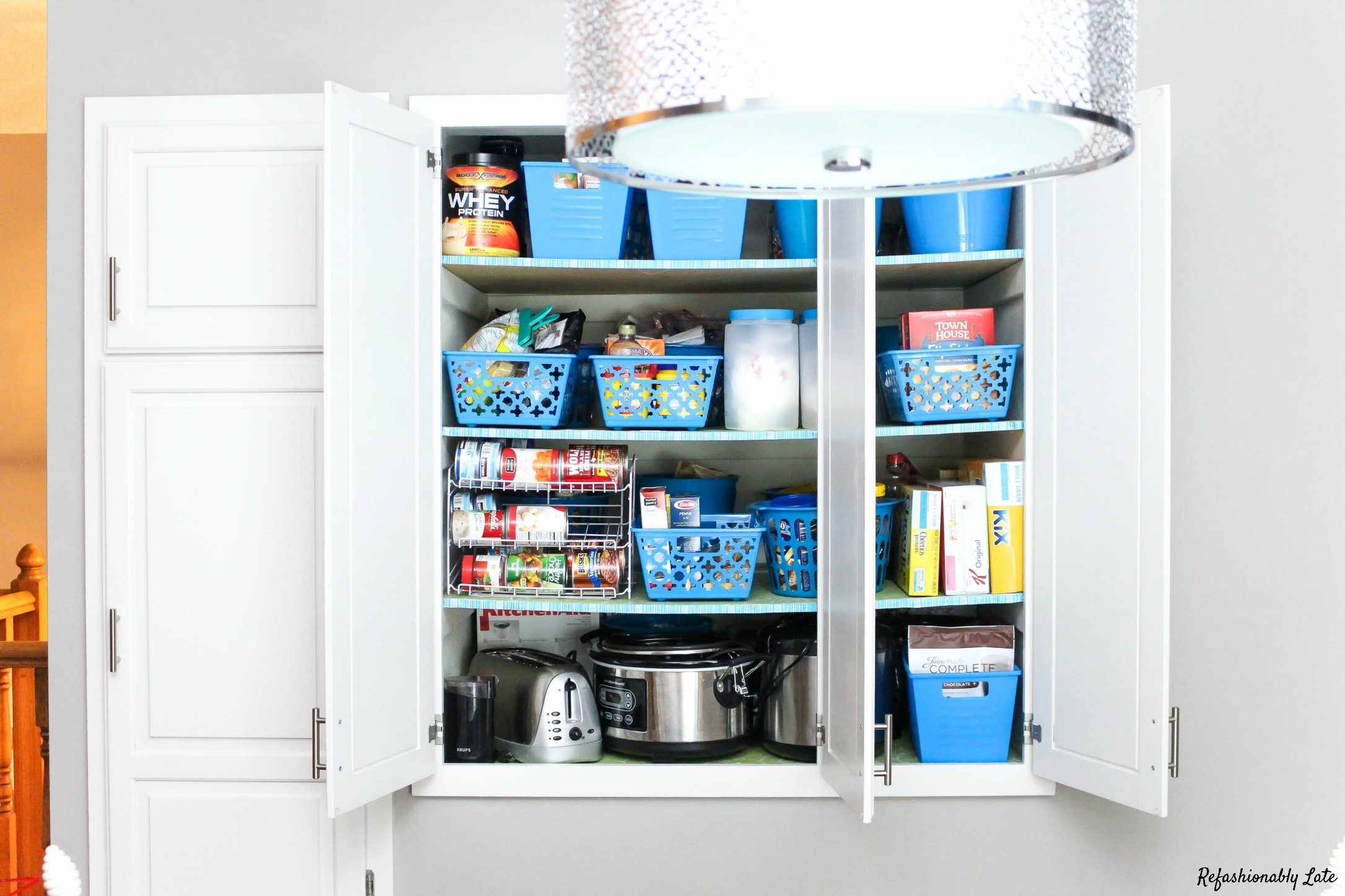 white cabinet doors open looking into organized pantry with dollar store blue bins