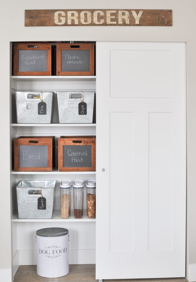 white pantry with grocery sign on tip with wood and metal baskets