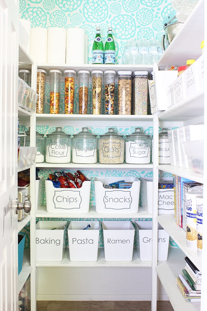 floral blue wallpaper inside of organized pantry with white bins and labeled food