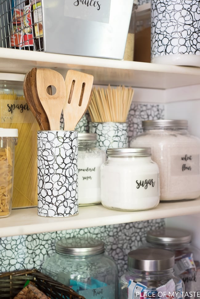 beautiful black and white decor inside of an organized pantry with wooden spoons front and center
