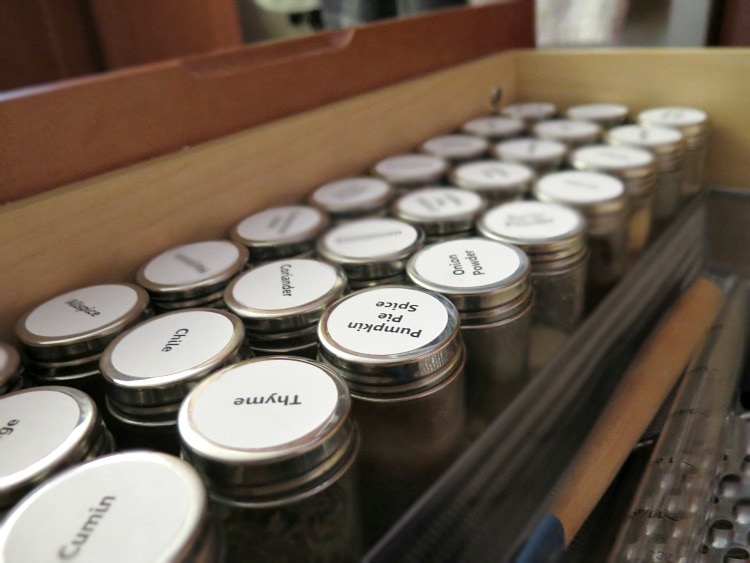 tin spice jars arranged neatly in a drawer with white labels