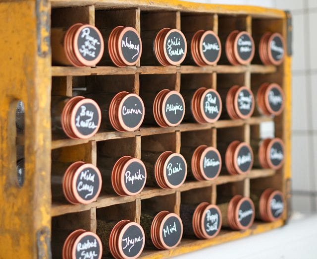 copper spice jars in a wooden display box