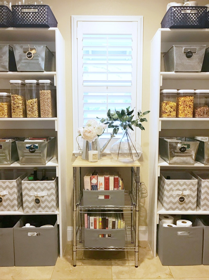 pantry with a plantation shutter window and chevron bins and metal bins storing food