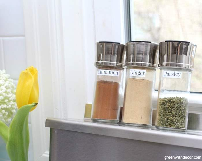 glass and stainless steel spice jars sitting on top of a shelf made for your oven