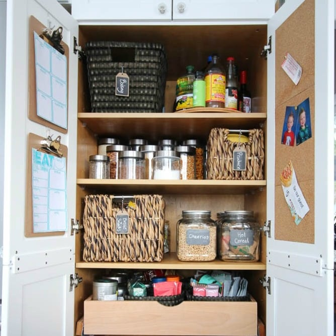 white pantry with cork board on the doors and woven basket and glass containers for food organization