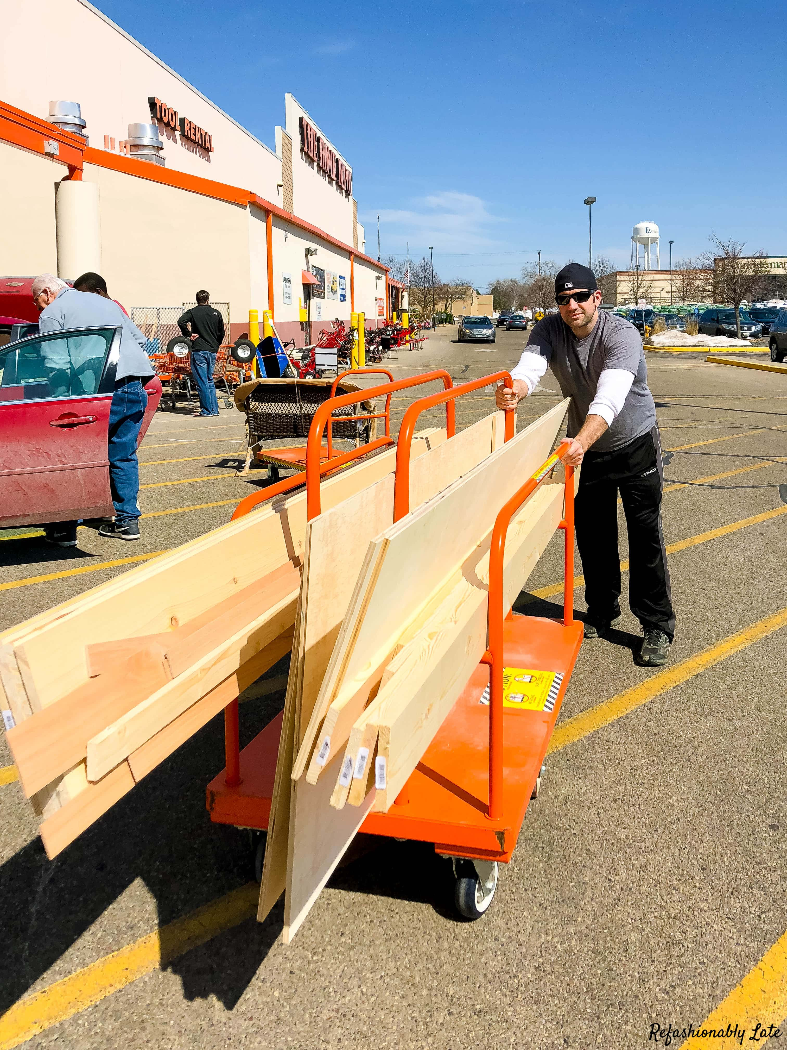 man wheeling an orange cart full of wood in front of Home Depot