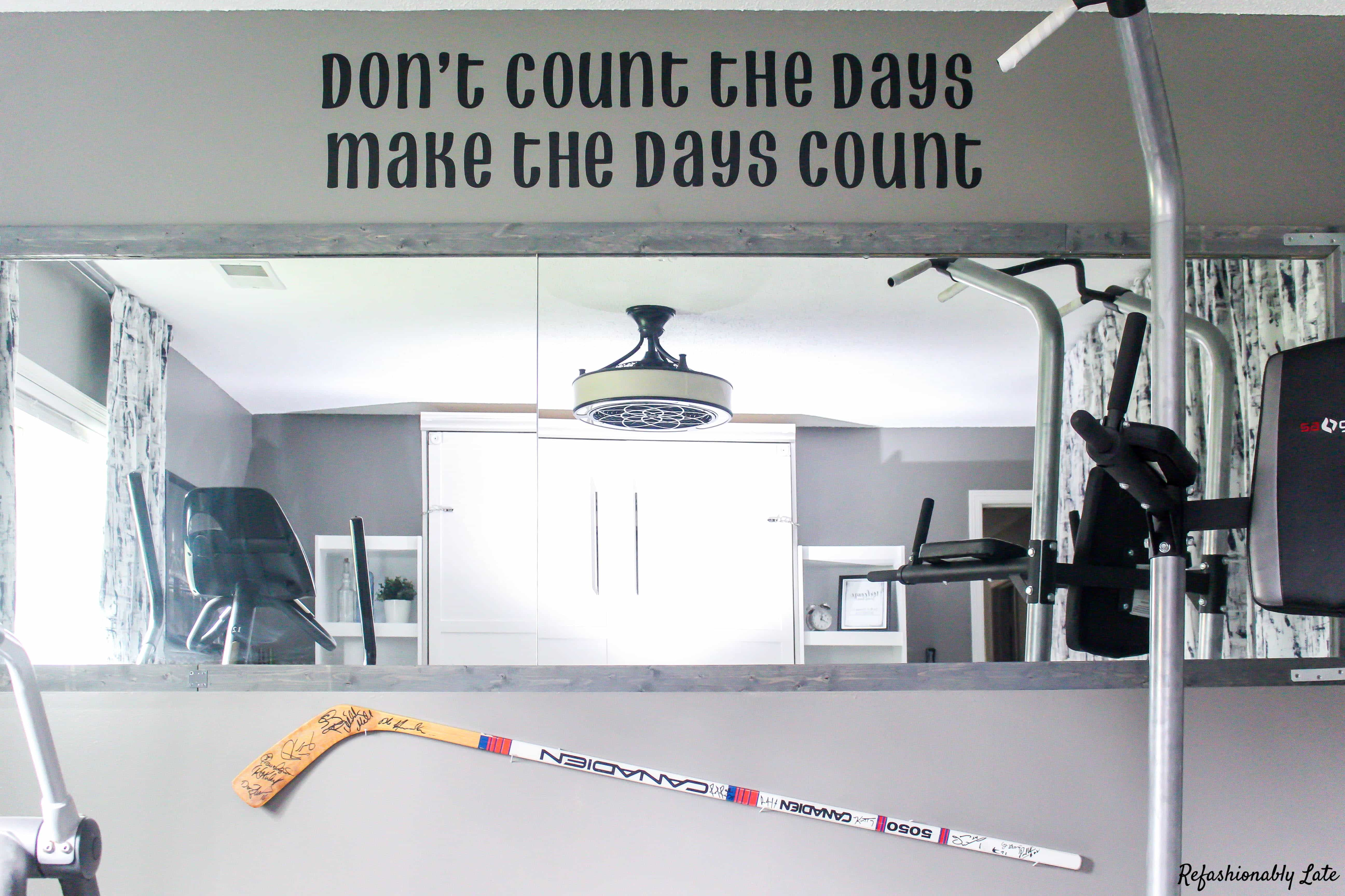 hockey stick on the wall with gym equipment and a mirror which shows a queen size murphy bed and a quote at the top that reads don't count the days make the days count