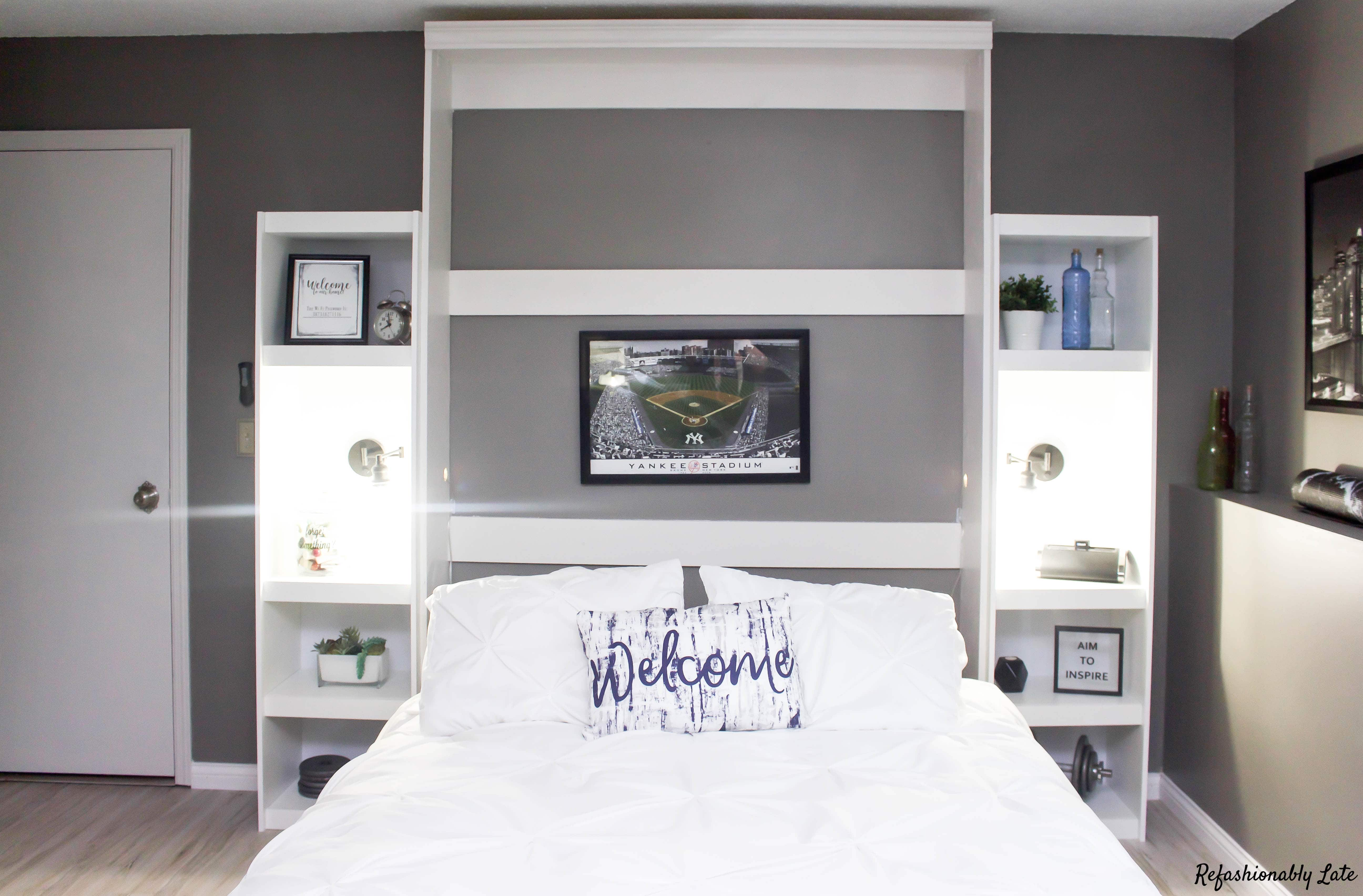 murphy bed folded down with a pillow with the text welcome and two shelves on either side with built in lights turned on