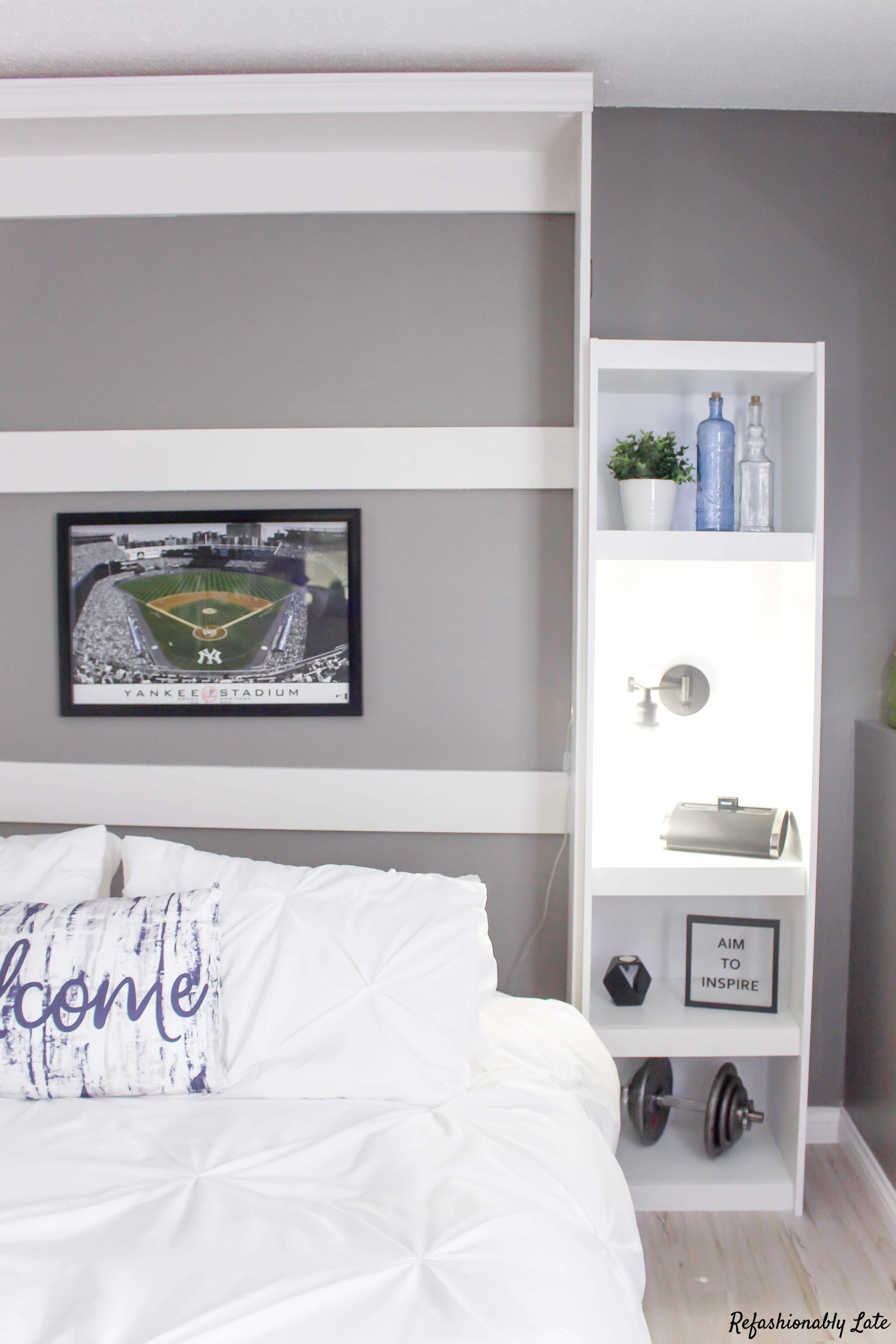 murphy bed folded down with a pillow with the text welcome and one shelf with aim to inspire picture and light on