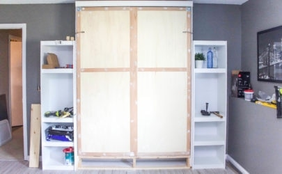 murphy bed with filled in holes where the molding was nailed in with two white shelves on either side and white maple allure vinyl flooring