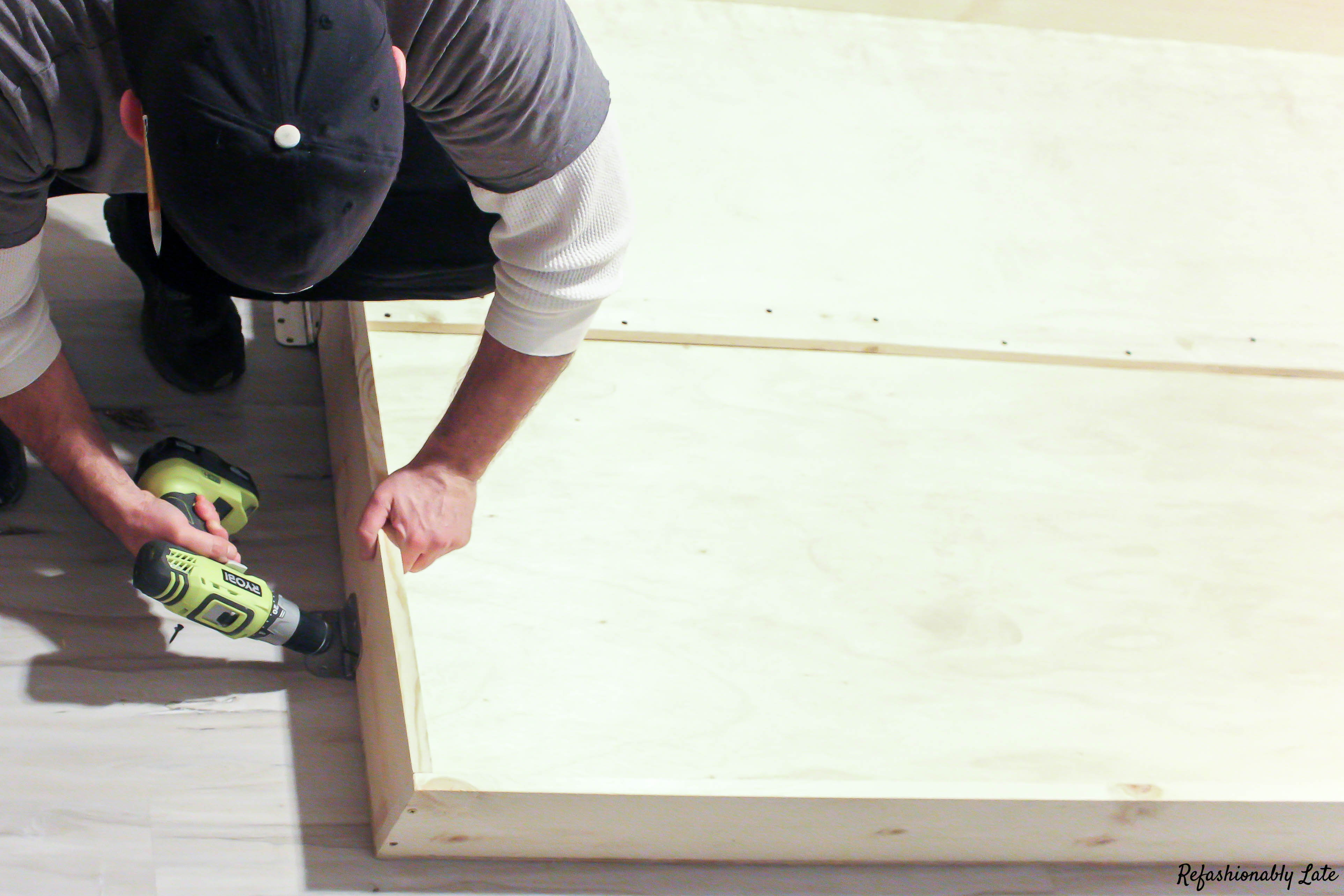 man attaching door hinges to bed frame on a white maple floor